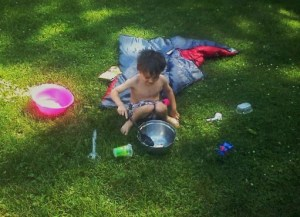 Superhero Son playing in the yard with bowls of water.  He said he was making a cake!